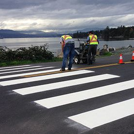 man painting white stripes on road